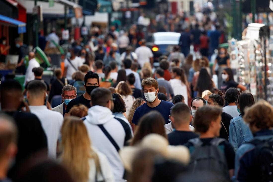 People wearing protective face masks walk in a busy street in Paris as France reinforces mask-wearing in public places as part of efforts to curb a resurgence of the coronavirus. — Reuters