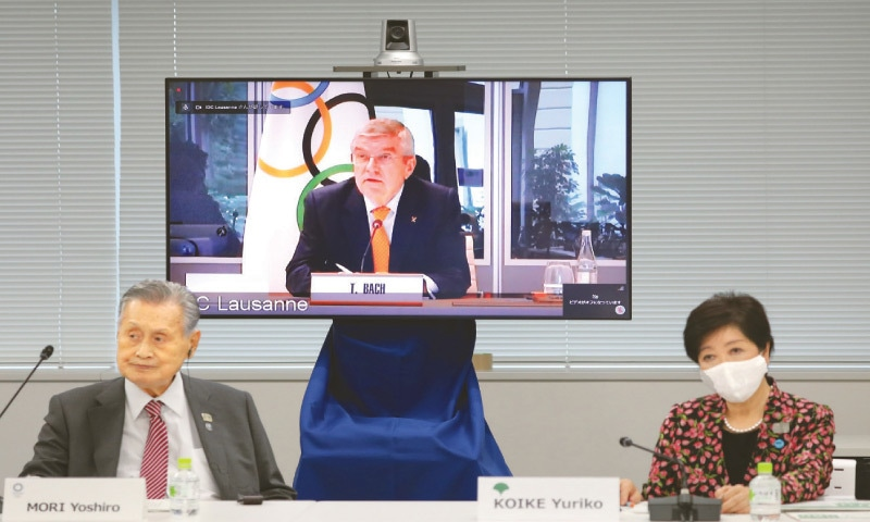 PRESIDENT of the Tokyo 2020 Organising Committee Yoshiro Mori (L) and Tokyo Governor Yuriko Koike listen as IOC president Thomas Bach (on screen) speaks during a video meeting on Thursday.—AFP