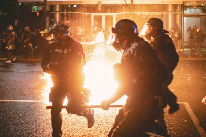 PORTLAND (Oregon): Police officers take evasive action as a molotov cocktail is thrown towards them during unrest following a grand jury's decision in the Breonna Taylor case.—Reuters