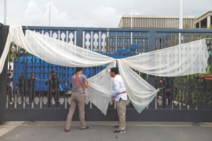 BANGKOK: Protesters attach a white ribbon to a gate of the parliament on Thursday.—Reuters