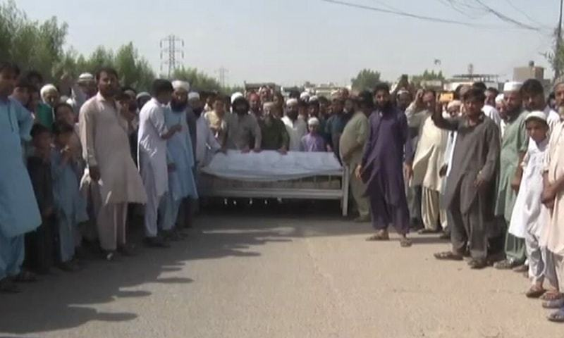 Relatives of the deceased boy protest near Shafiq Mor along with his coffin on Friday. — DawnNewsTV
