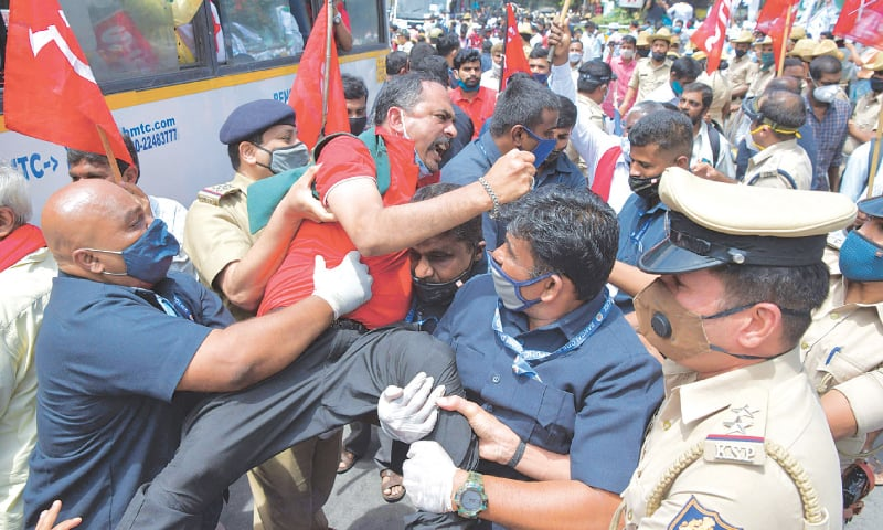 BANGALORE: Protesters trying to block a road scuffle with police attempting to arrest one of them during a farmers' rally on Friday.—AFP