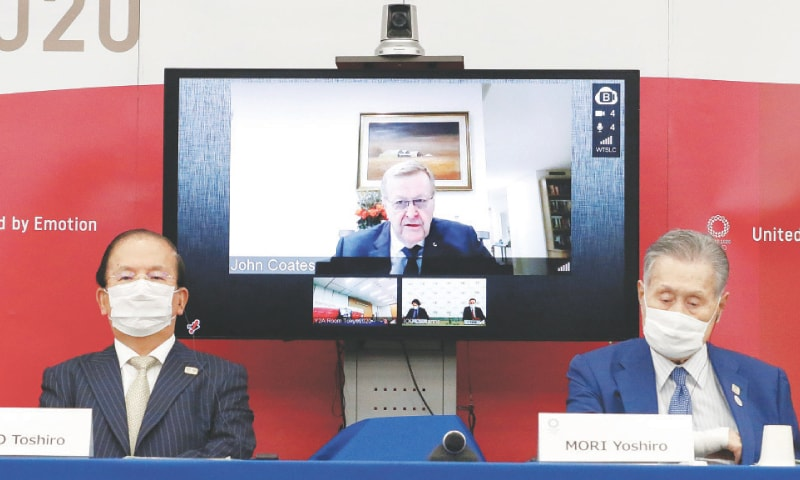 JOHN Coates, Chairman of Coordination Commission for the Games of the XXXII Olympiad Tokyo 2020, speaks on screen during a joint press conference as Tokyo 2020 CEO Muto Toshiro (L) and its president Mori Yoshiro look on at the Harumi Island Triton Square Tower on Friday.—Reuters