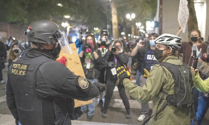 Portland (Oregon, US): A police officer confiscates a shield from a protester.—AFP