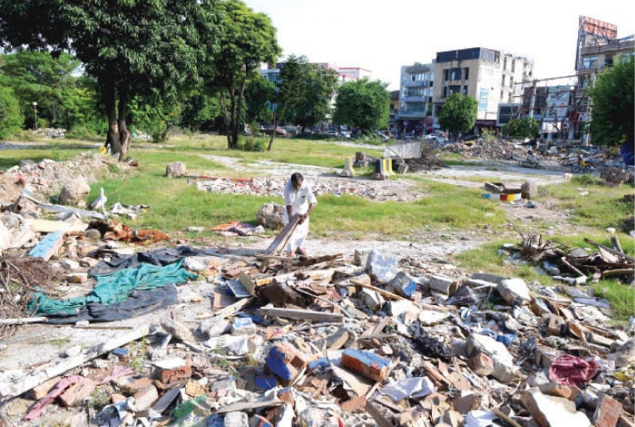 A ragpicker sifts through debris at a park in Rawalpindi's Commercial Market. The park was demolished to make way for a car park. — White Star