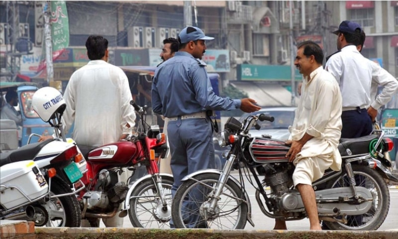 A traffic police official fines a motorcyclist in Punjab. — Photo couretsy Traffic Police Punjab website