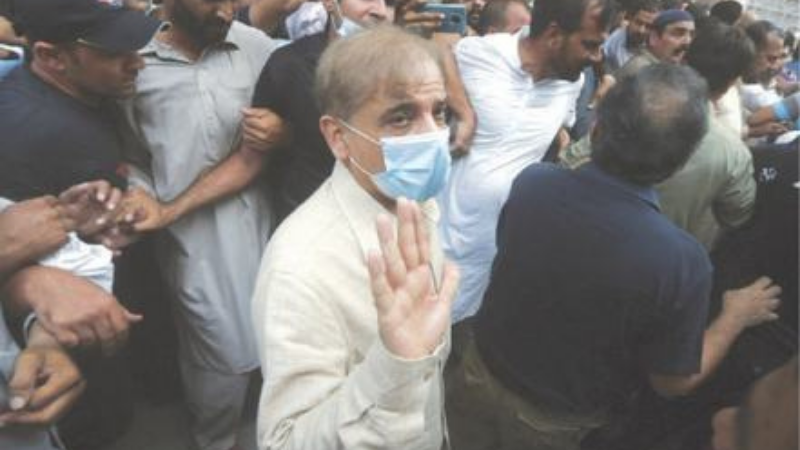 LAHORE: Opposition Leader Shahbaz Sharif waves while being escorted by officials at the Lahore High Court after his bail was rejected on Monday. — AP