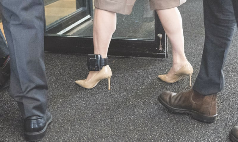 VANCOUVER (British Columbia, Canada): Huawei CFO Meng Wanzhou, while wearing her ankle monitoring device, walks into a court with her security detail to resume her fight against extradition to the United States.—AFP
