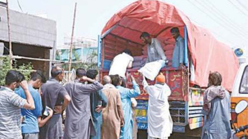 SIALKOT: In this Sept 25 photo, people wait for their turn to buy wheat flour from a government distribution truck on Kashmir Road. — APP