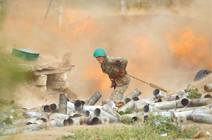 YEREVAN (Armenia): A soldier fires an artillery piece towards Azeri positions during fighting on Tuesday.—AFP