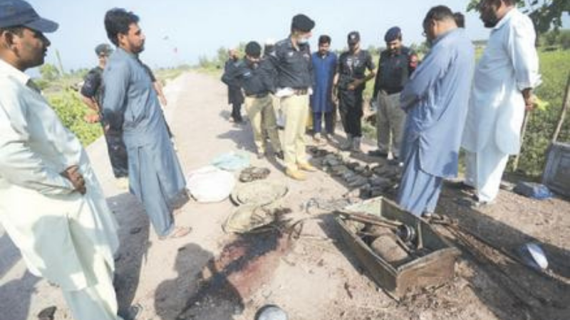 POLICE officers inspecting the site of the explosion in Nowshera on Tuesday. — AP