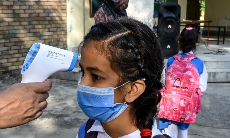 A teacher (L) checks the body temperature of a child wearing a facemask at the entrance of a junior campus school upon arrival in Islamabad on September 30. — AFP