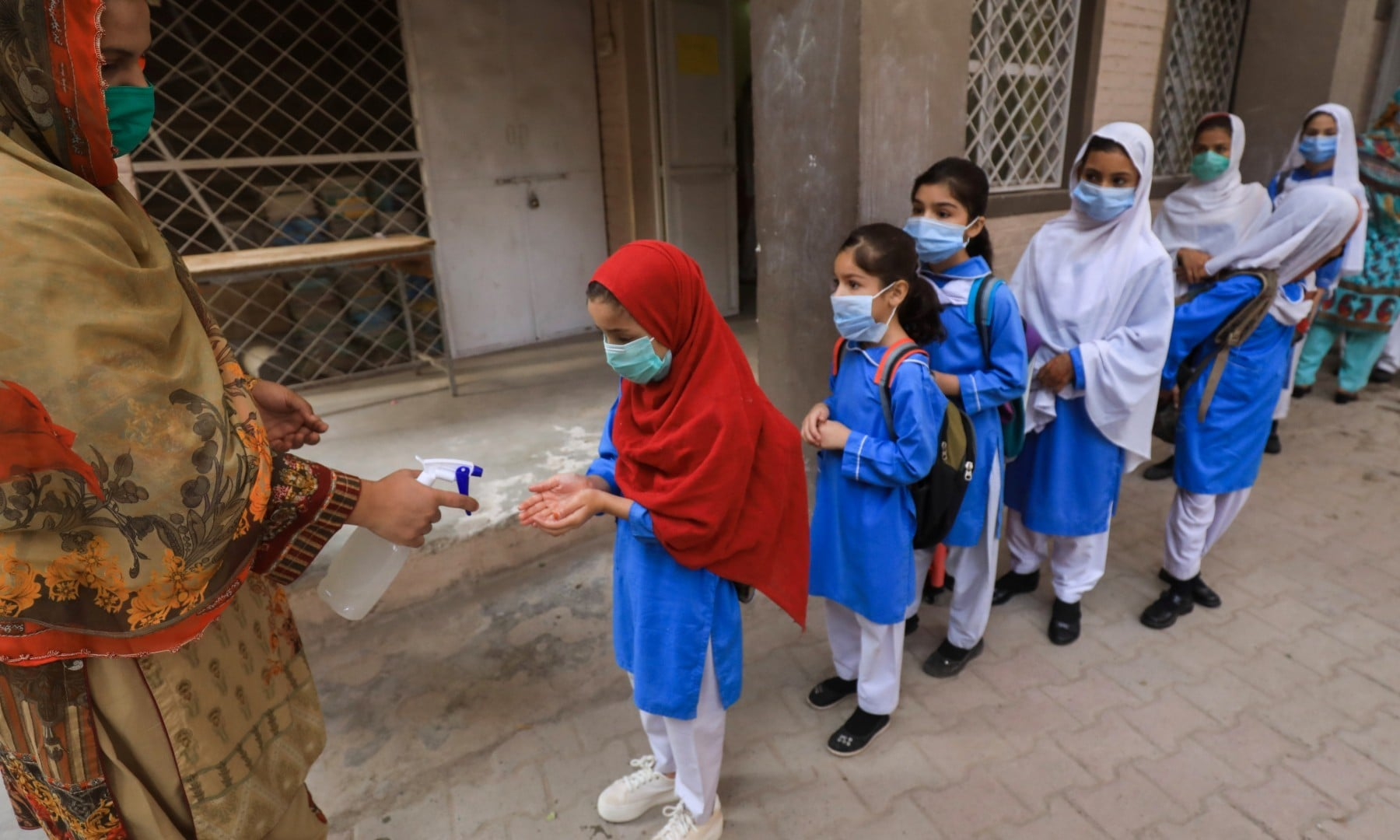 Students wear protective masks as they get their hands sanitised before entering a class in Peshawar on September 30. — Reuters