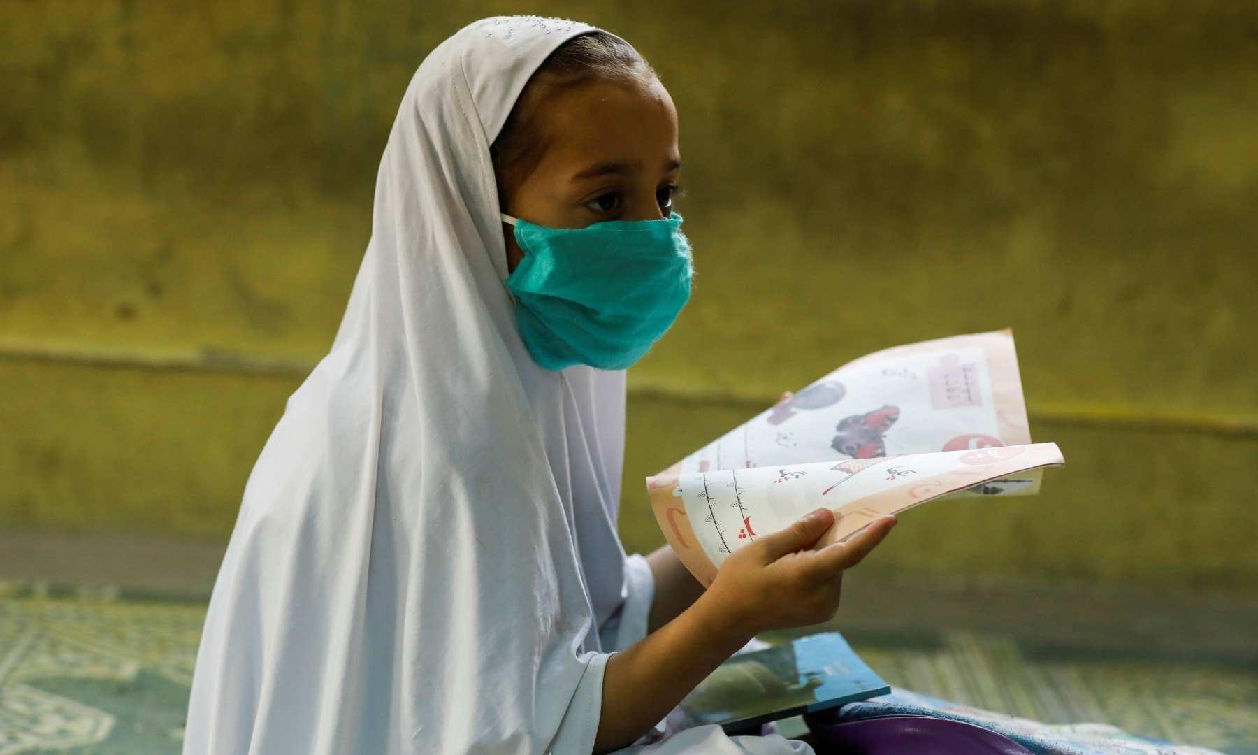 A student wearing a protective mask sits on the floor in Peshawar on September 30. — Reuters