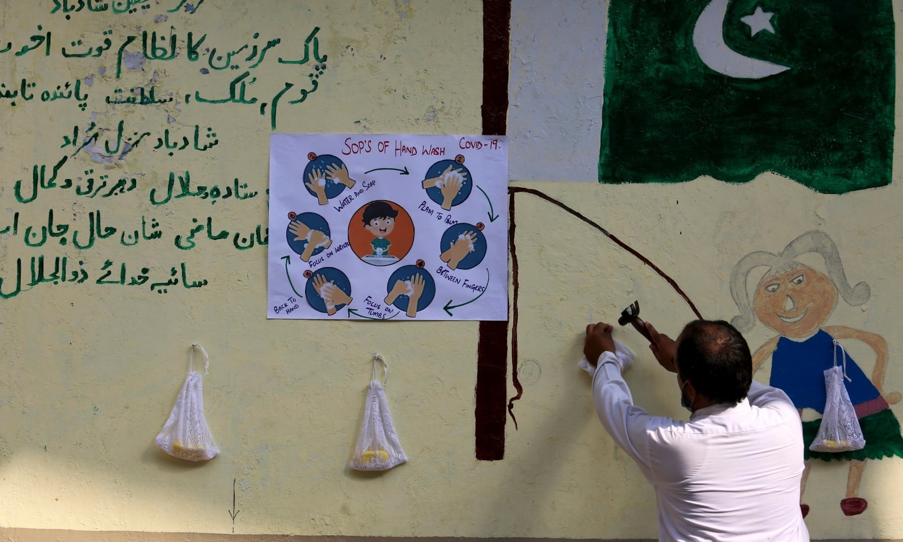 A worker hangs soaps and a placard of hand washing information for student at a primary school in Peshawar on September 30. — AP