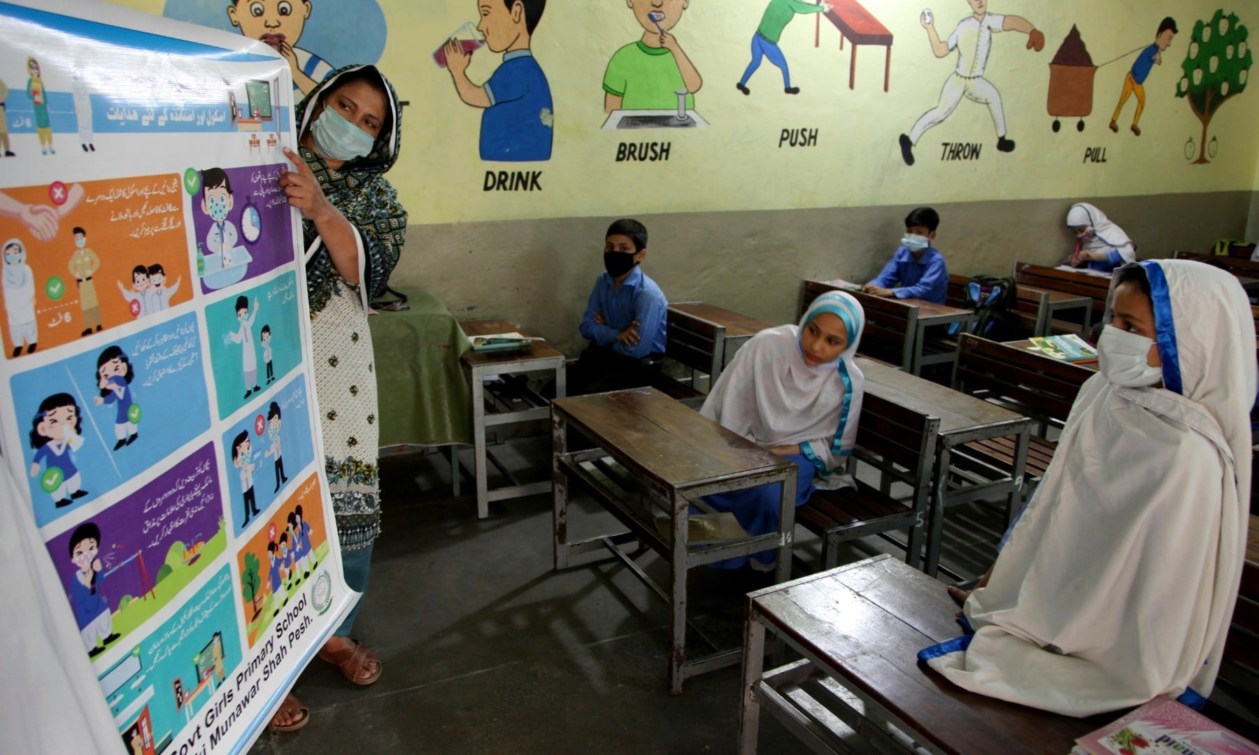 A teacher briefs about precautions of the coronavirus to students at a primary school in Peshawar on September 30. — AP