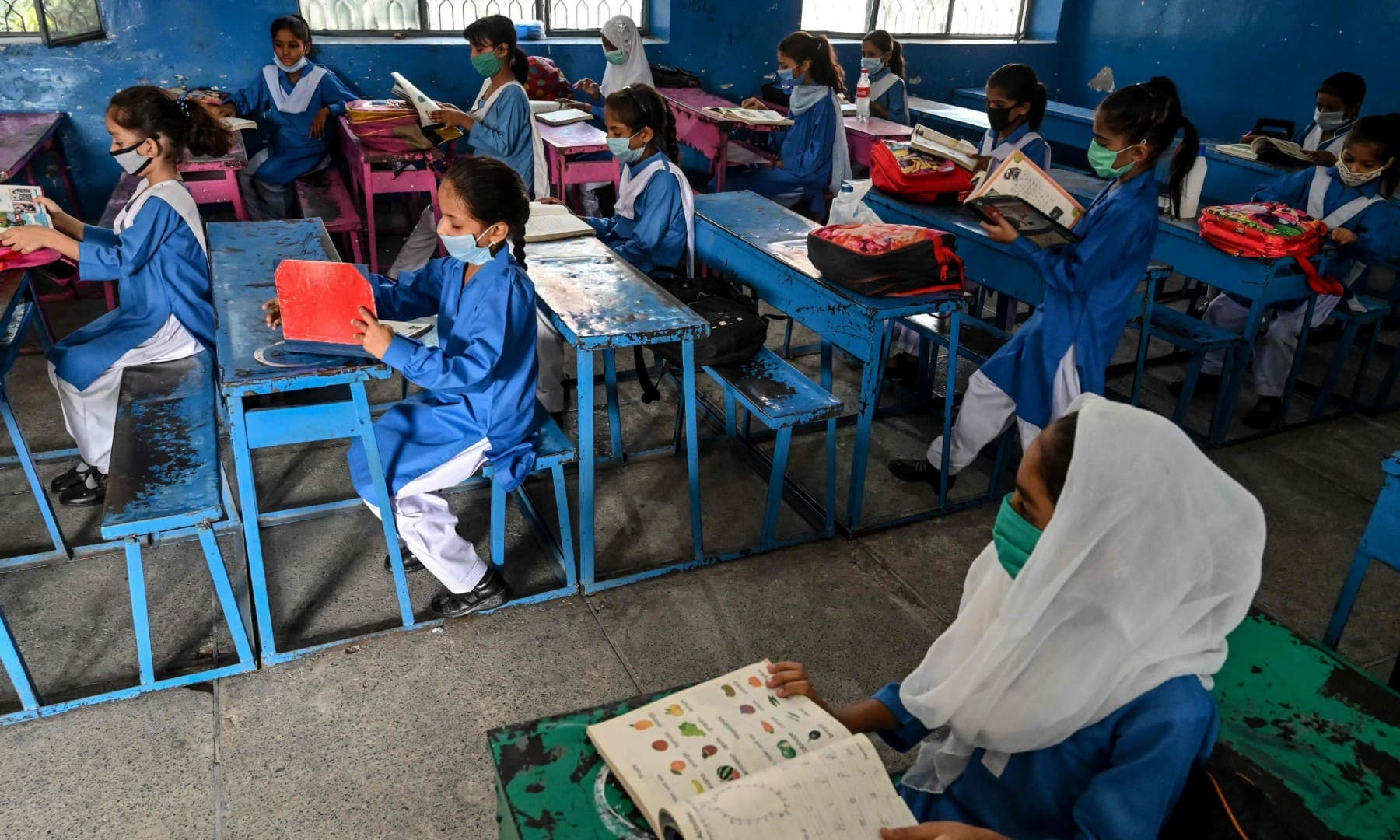 Children wearing facemasks attend a class at a school in Lahore on September 30. — AFP