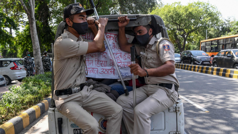 Police personnel sit in a vehicle after detaining protestors during a demonstration outside the Uttar Pradesh Bhawan (state house) in New Delhi on Sept 30, 2020, a day after a 19-year-old woman who was allegedly gang-raped died from her injuries near Bool Garhi village in the UP state. — AFP