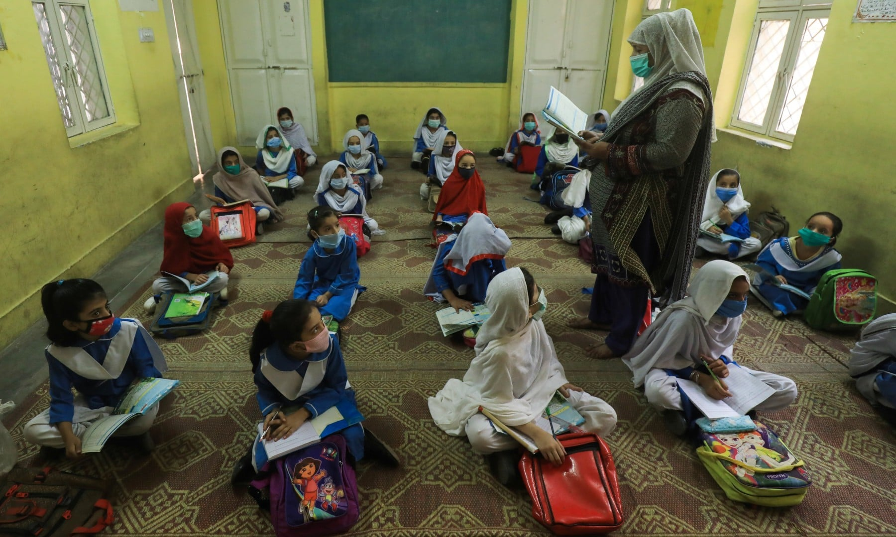 Students wear protective face masks while maintaining a safe distance while they sit on the floor in Peshawar on September 30. — Reuters