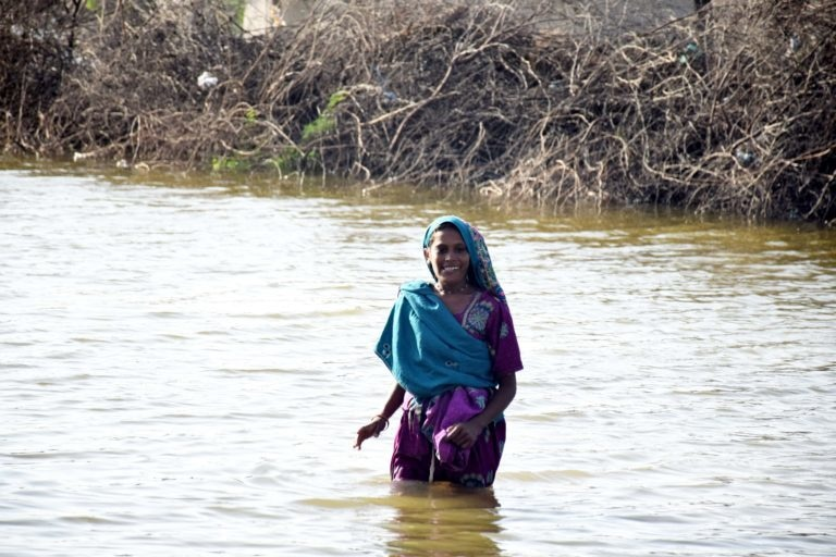 A village woman wades through thigh deep water in a village of Kali taluka of Tharparkar district to reach her makeshift roadside tent. — Photo by Yasir Rajput/The Third Pole