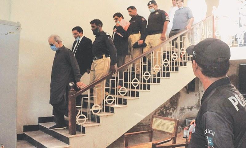 عدالت کی جانب سے نیب کے ریمانڈ میں دیے جانے کے بعد مخدوم جلیل الزمان وکلا اور پولیس کے ہمراہ سیڑھیوں سے نیچے اتر رہے ہیں— فوٹو: پی پی آئی