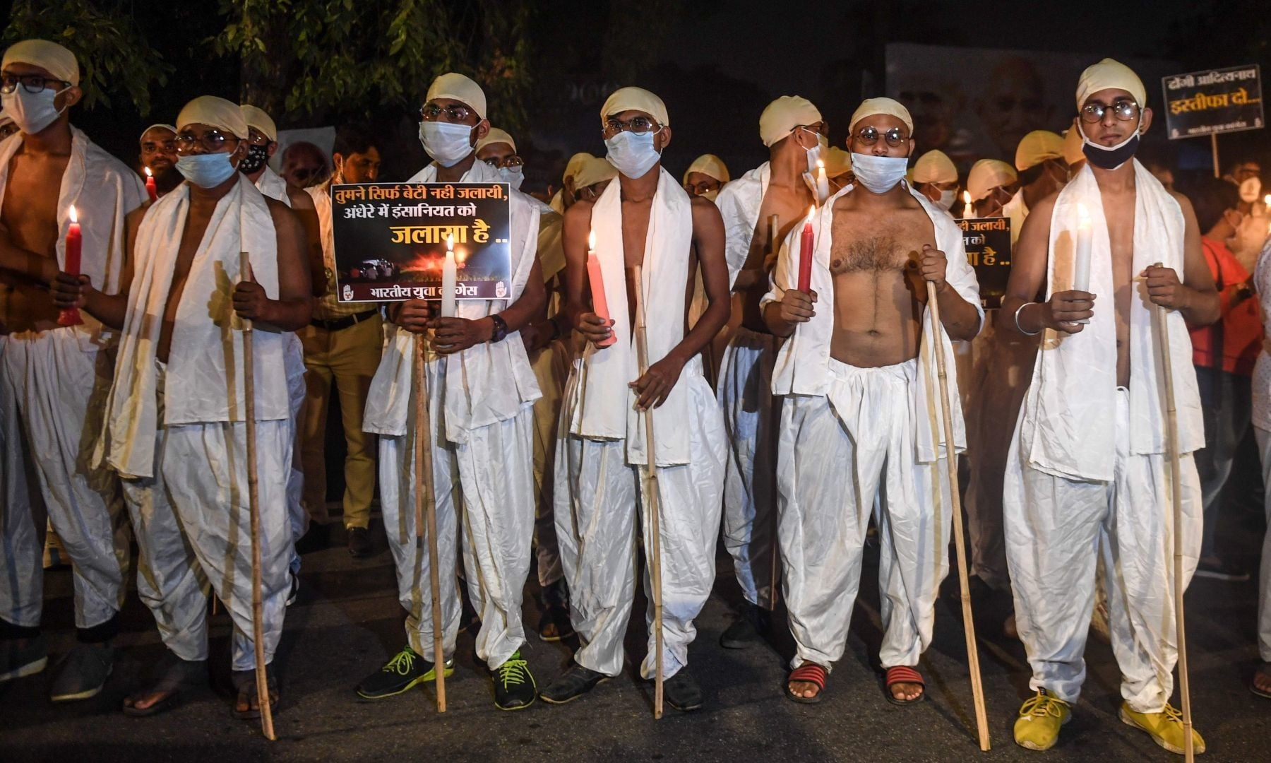 Activists of Indian Youth Congress, dressed as Mahatma Gandhi on the occasion of his birth anniversary marked as the 'Gandhi Jayanti' day, attend a candle march protest against the gang-rape of a woman in Uttar Pradesh, in New Delhi on October 2. — AFP