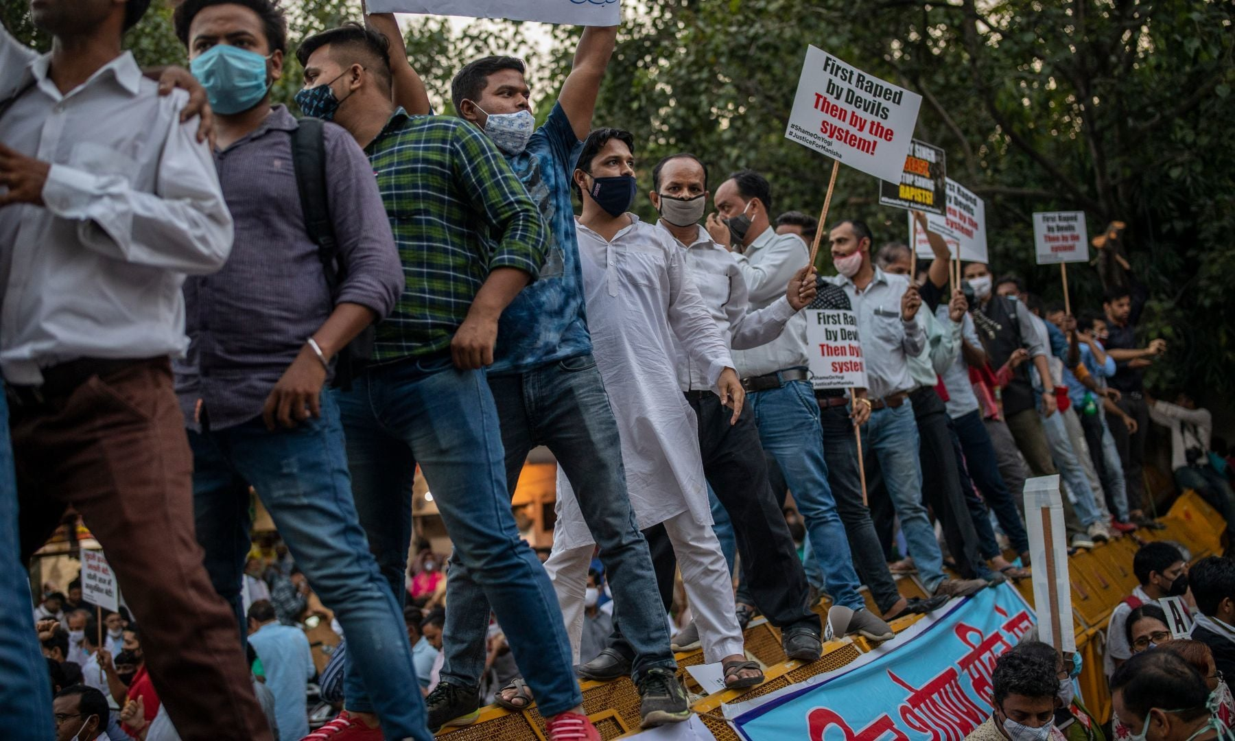 Protestors stand on a barricade and raise their voices against the gang rape and killing of a woman, in New Delhi, India, Friday. — AP