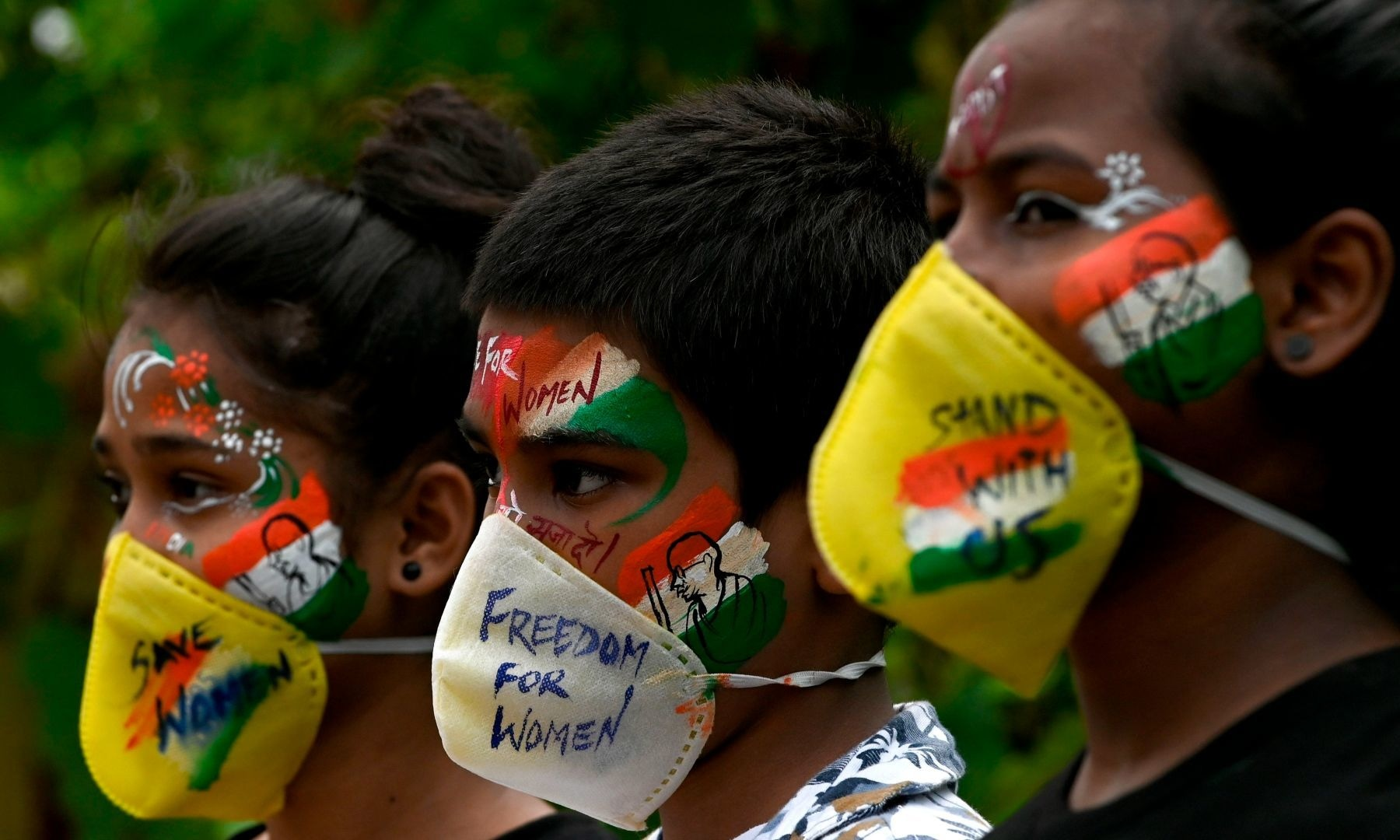 Students look on after getting their face painted to condemn the gang-rape a woman, in Mumbai on October 2. — AFP