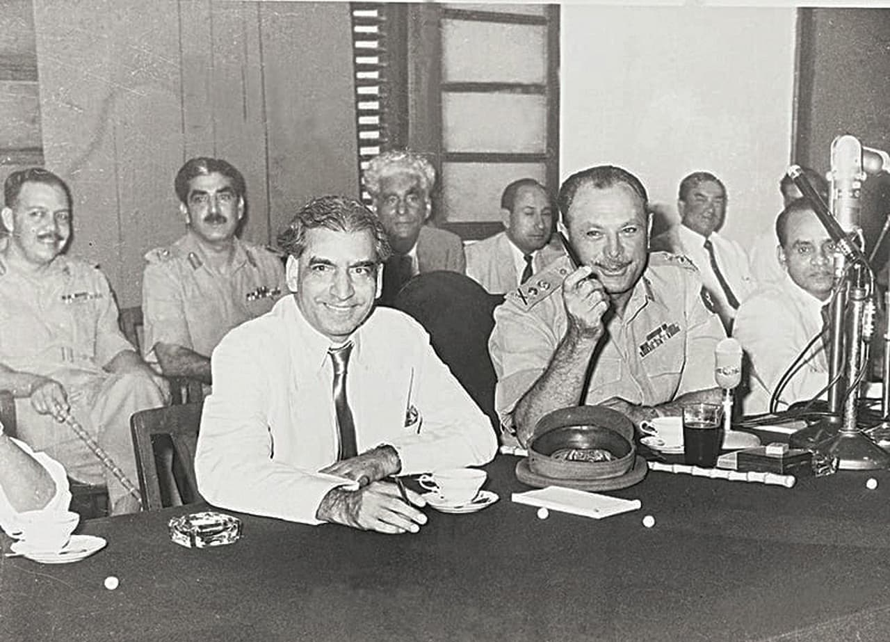 General Ayub Khan, Supreme Commander and Chief Martial Law Administrator, smiling after having addressed the nation on Radio Pakistan on October 8, 1958 – a day after he abrogated the Constitution and imposed Pakistan's first Martial Law. He is flanked here by senior bureaucrat Aziz Ahmed (left) and Lt-Gen Majeed Malik (right) who was instrumental in making it all happen. Seen behind them are Lt-Gen Yahya Khan (extreme left) and Zulfiqar Ali Bukhari (second from left) | Hasan Bozai