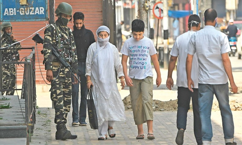 In this June 2020 file photo, Indian paramilitary soldiers stand guard as people walk through central Srinagar. — AFP