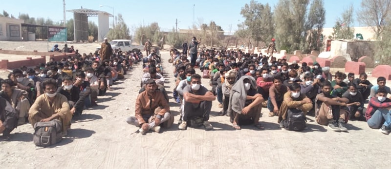 TAFTAN: Hundreds of illegal migrants wait to get registered for their entry into Pakistan after being deported by Iranian authorities at Raahdari Gate on Sunday.—Dawn