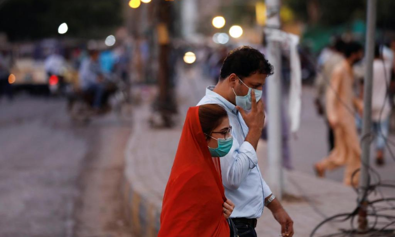 In this file photo from August, a man and a woman wear protective masks while walking along a street in Karachi. — Reuters