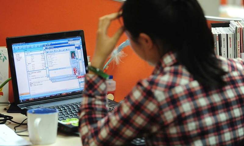 This file photo shows a woman working online in her cubicle at an office in Beijing. — AFP