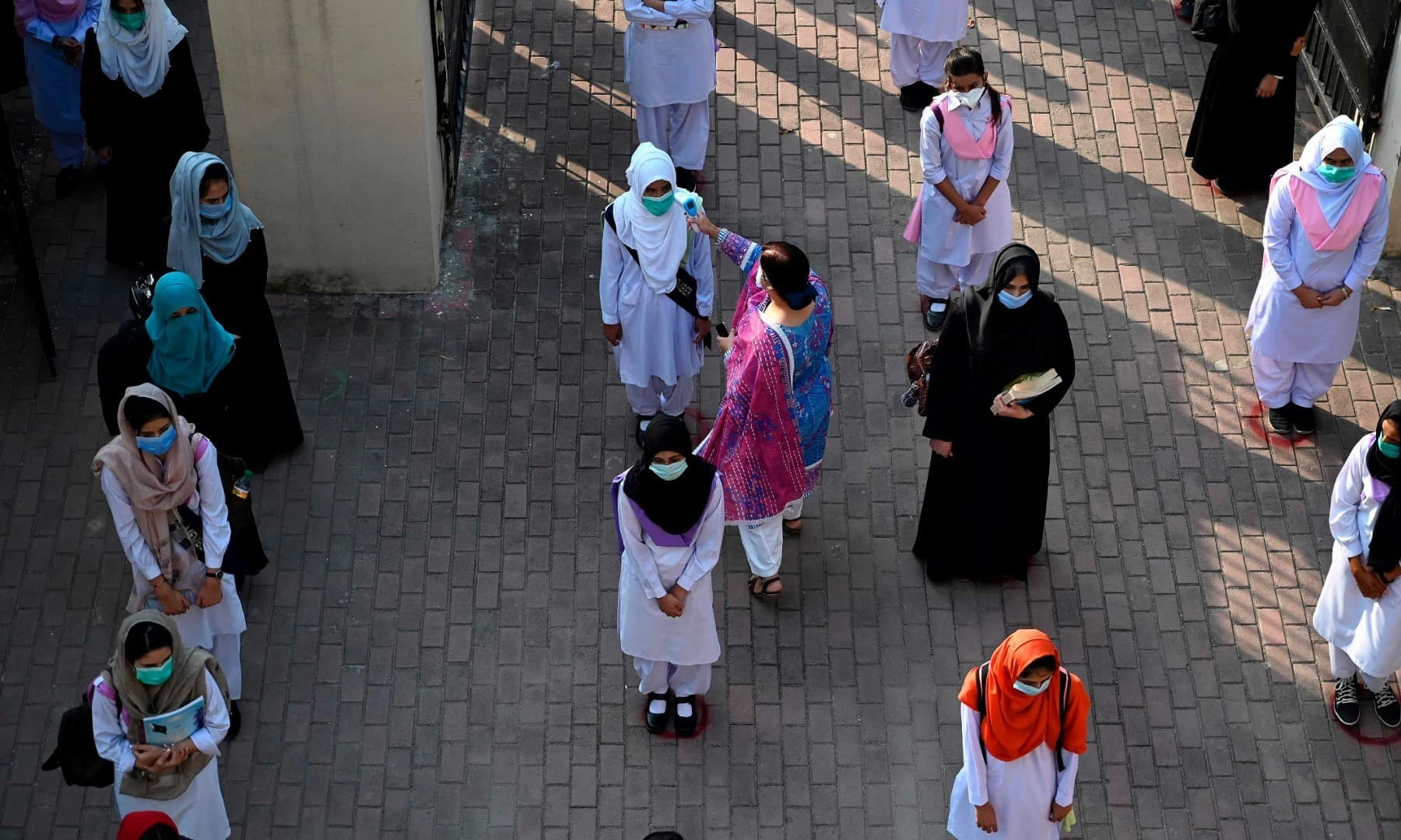 A teacher checks the body temperature of students at the entrance of the Islamabad Model College of Commerce for Girls in Islamabad on September 15. — AFP/File