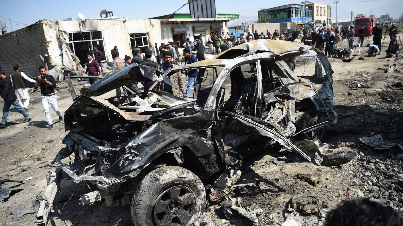 Afghan security personnel and civilians gather next to a damaged car at the site of a car bomb attack in Kabul on March 17, 2018. ─ AFP/File