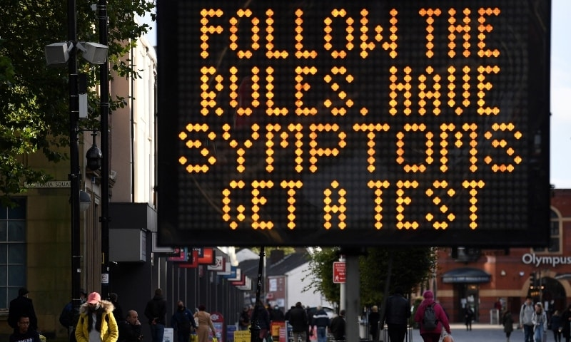 A woman walks near an electronic road sign displaying Covid-19 information in Bolton town centre on October 7. — AFP