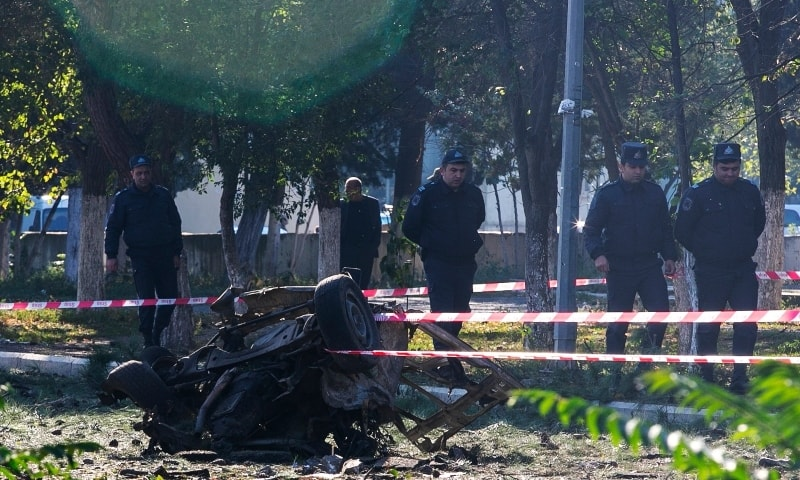 Members of Azerbaijan's security forces, inspect the damage following an overnight missile attack by Armenian forces, in the city of Ganja,  on October 8. —  AP
