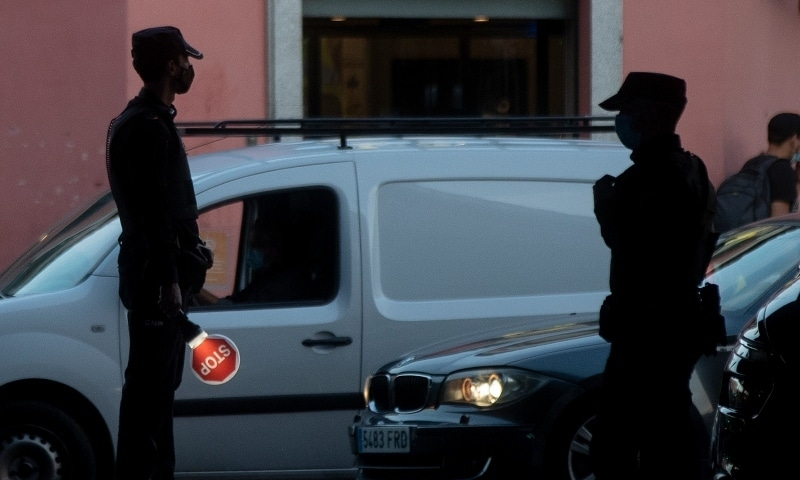 Police prepare to stop vehicles at a control point in the Vallecas district of Madrid on October 9. — AP
