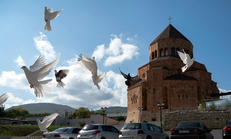Pigeons fly near Holy Mother of God Cathedral in Stepanakert during a military conflict in the separatist region of Nagorno-Karabakh on October 9. —  AP