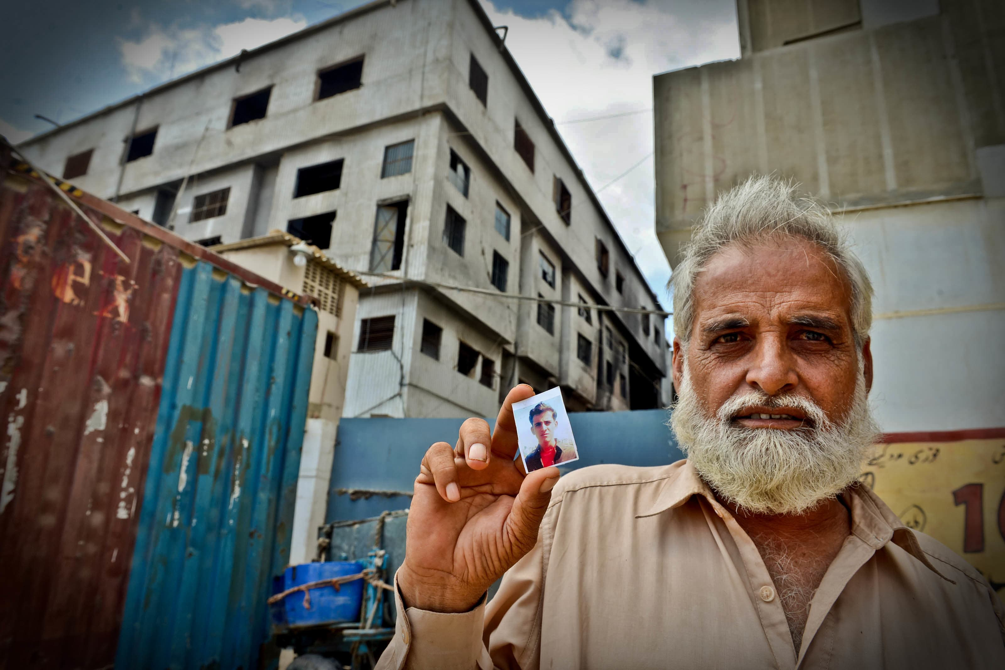 Mohammad Jabbar, a factory worker, shows a photograph of his son who lost his life in the Baldia factory tragedy | White Star