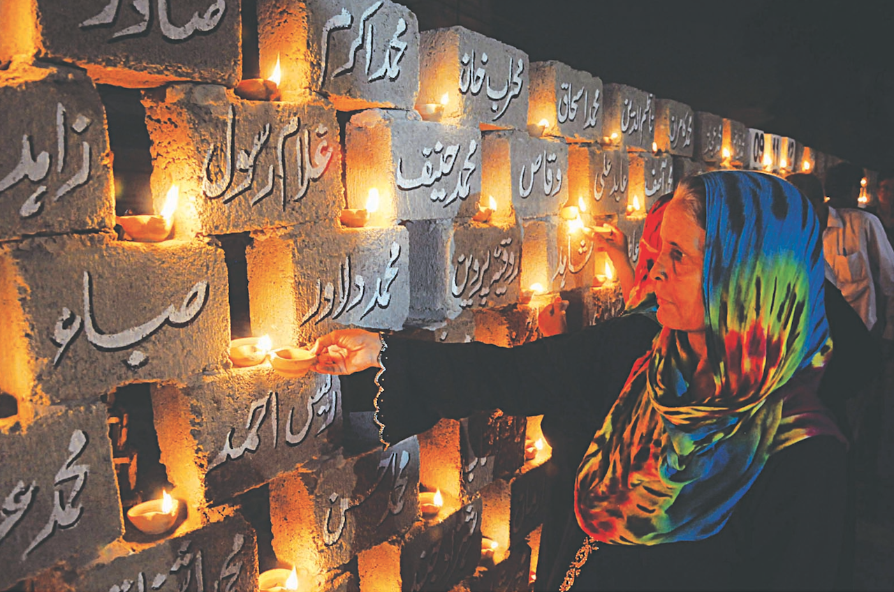 Relatives of the victims place oil lamps on a 'memorial wall' | White Star