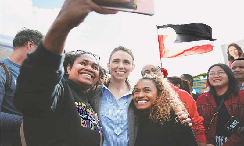 New Zealand's Prime Minister Jacinda Ardern takes pictures with supporters during a campaign outing at Otara Market in Auckland on Saturday. — Reuters