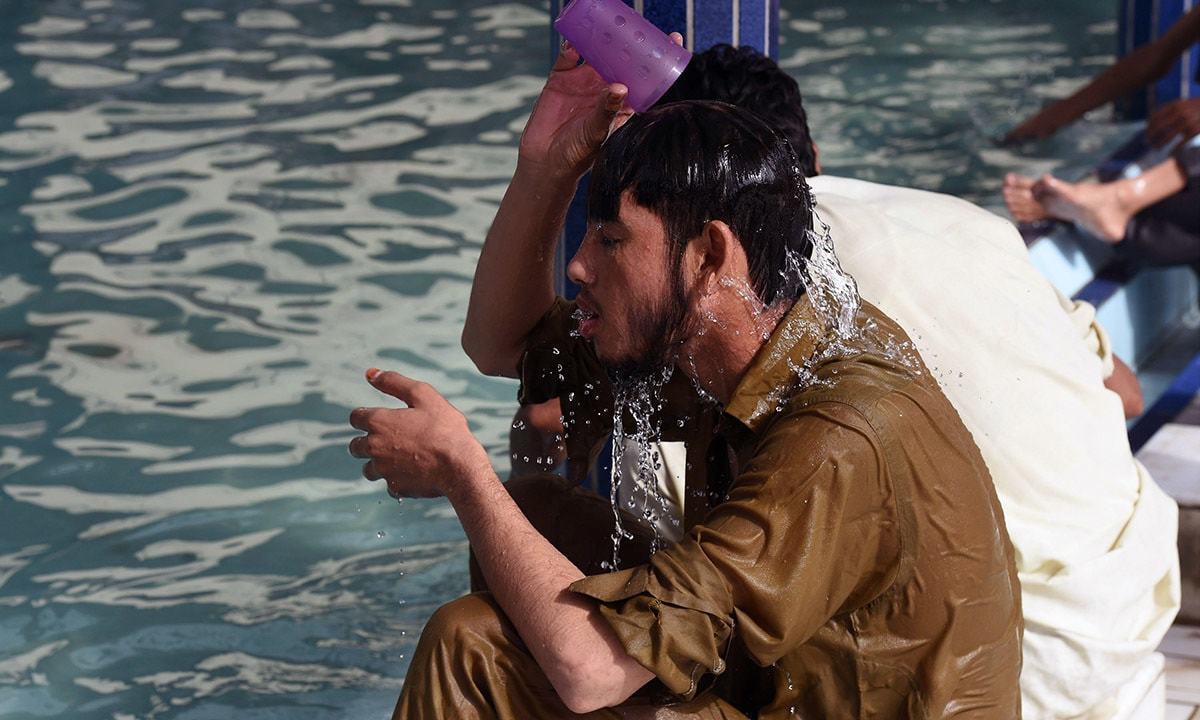 A man cools down with water at a mosque during the 2015 heatwave in Karachi. ─ AFP/File