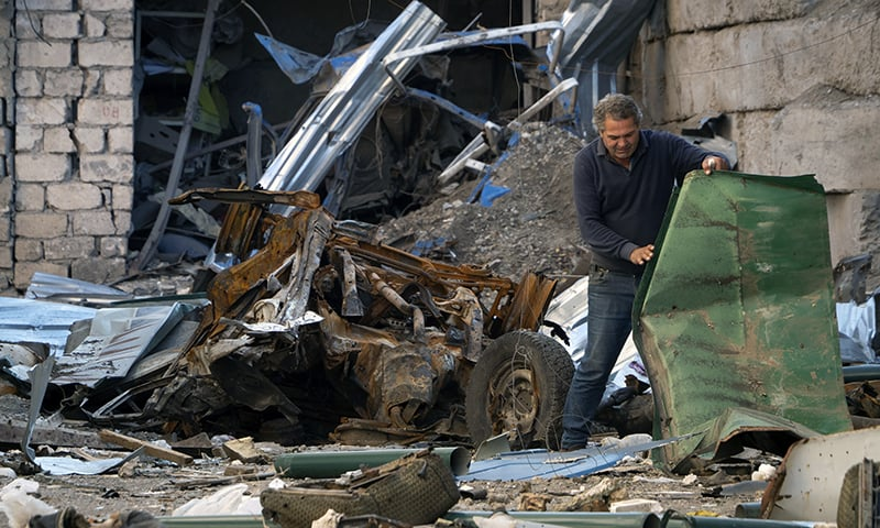 A man moves debris in the yard of a house destroyed by shelling by Azerbaijan's artillery during a military conflict in Stepanakert, the separatist region of Nagorno-Karabakh, on October 13. — AP