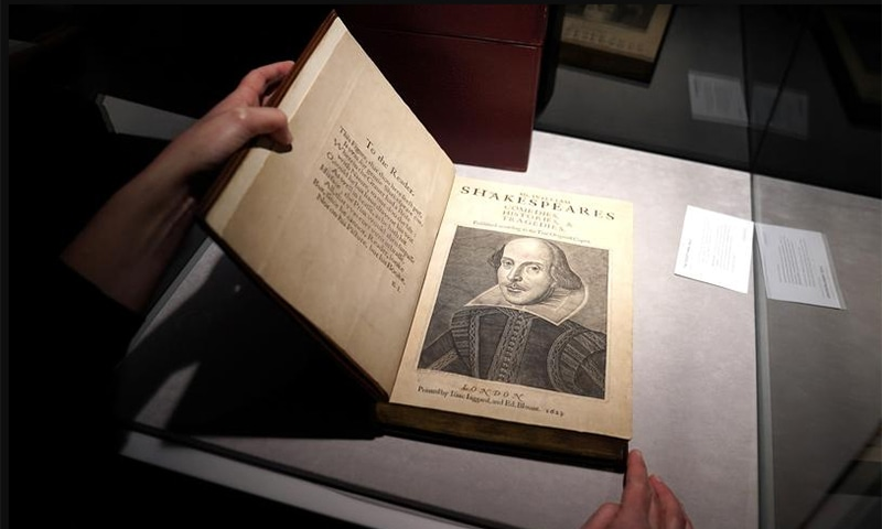 An employee of Christie's auctions holds a 1663 rare first folio of 36 Shakespeare works that was sold for a record 8.4 million dollars. — Reuters