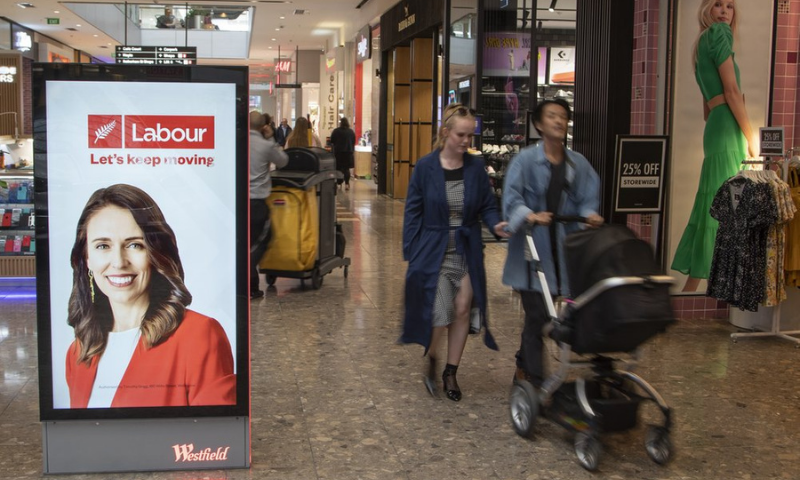 Shoppers walk past an electronic billboard showing a photo of New Zealand Prime Minister Jacinda Ardern in Christchurch, New Zealand. — AP