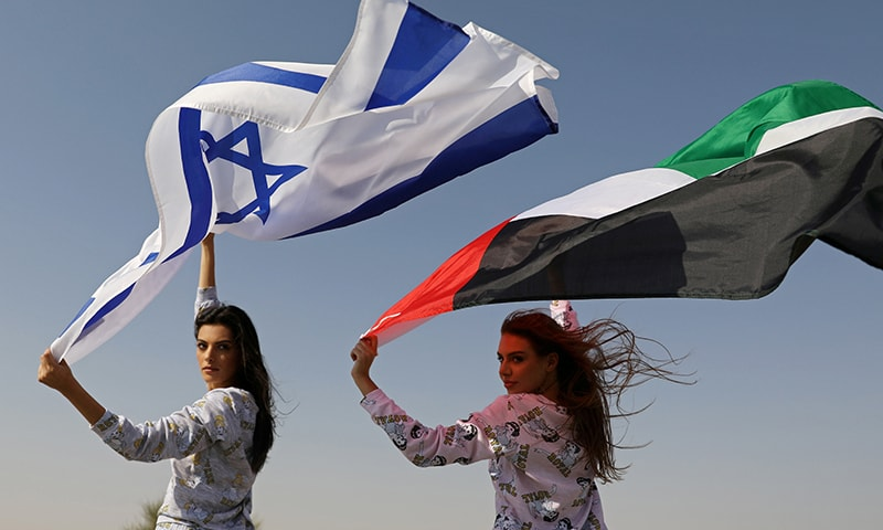 Israeli model May Tager, holding an Israeli flag, poses with Dubai-resident model Anastasia, holding an Emirati flag, during a photoshoot for FIX's Princess Collection in Dubai, UAE, on September 8, 2020. — Reuters