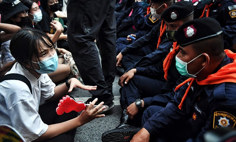 A young pro-democracy protester talks with police during a demonstration at a road intersection in Bangkok on October 15. — AFP