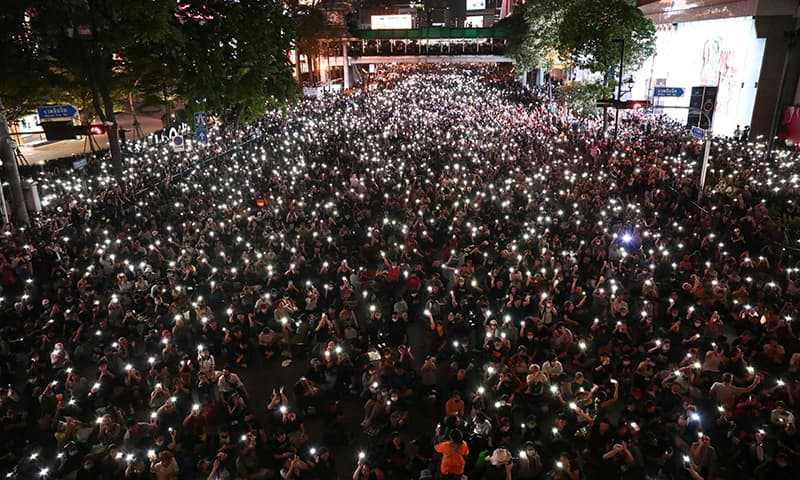 Pro-democracy protesters hold up flashlights on their phones during a demonstration in Bangkok on October 15. — AFP