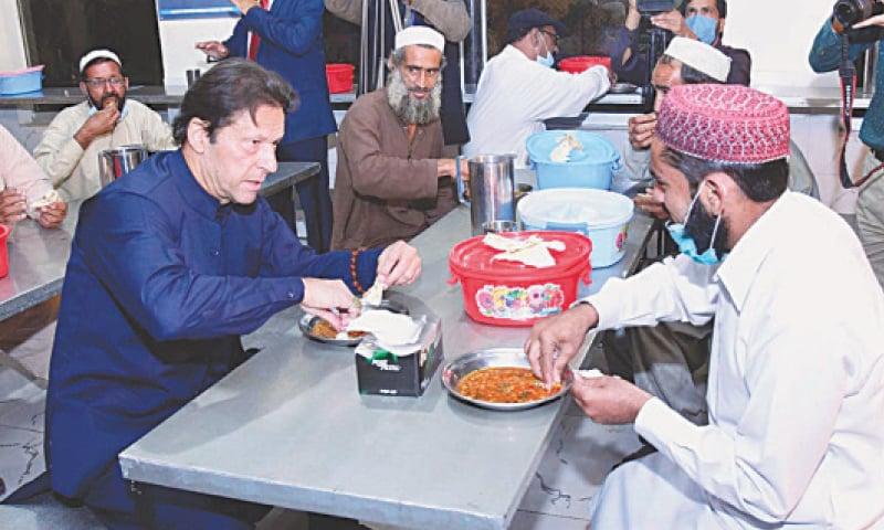 ISLAMABAD: Prime Minister Imran Khan having dinner during his visit to a shelter home at Peshawar Morr on Thursday.—APP